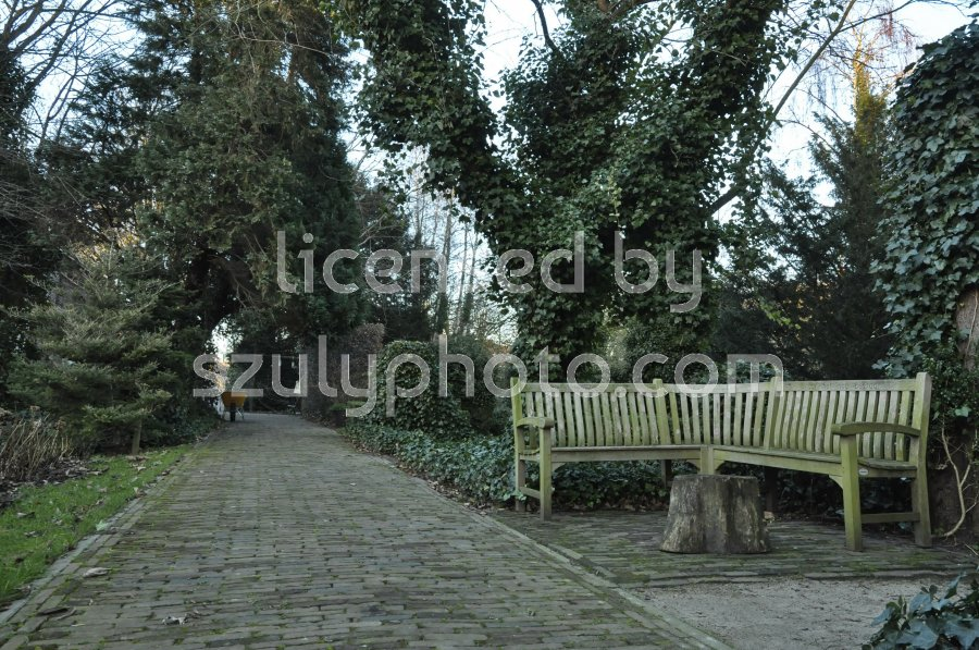 A wooden corner bench on the side of a pathway in the Huis te Vraag public garden, a national heritage site on the Rijnsburgstraat