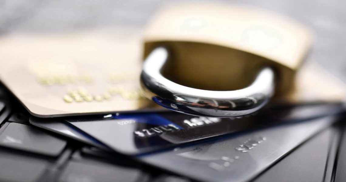 Side close-up view of credit cards accompanied by a padlock, on top of computer keyboard