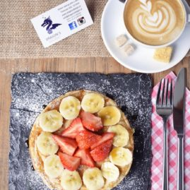 Overhead view of Enlish pancake with strawberries and banana, on top of a dark grey stone plate, accompanied by a cup of capuccino and the logo card of the cafe.