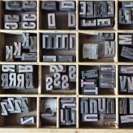 Overhead view of metallic letters in a wooden box, used for letterpress printing on a manual print machine