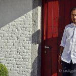 Sang Hoon Degeimbre, a Michelin star chef is standing in front of a red door under the setting sun, int eh garden of his restaurant.