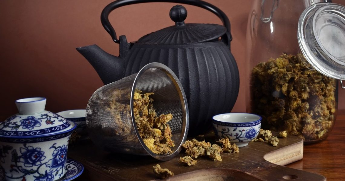 Side view of a black iron tea pot, accompanied by a white chinese tea set and a tea strainer with tea in it, on a wood cutting board, with a glass container in the background with chrysanthemum flower tea.