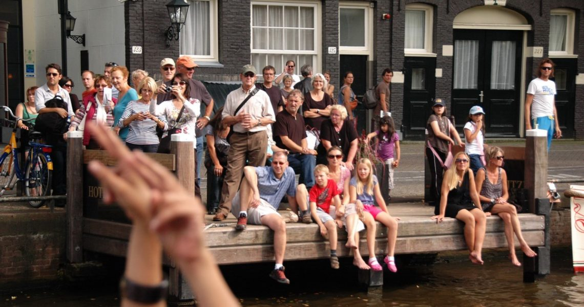 People in summer cloth, gathered at a public, hop on hop off boat stop in Amsterdam. Two hands blurred in the foreground.