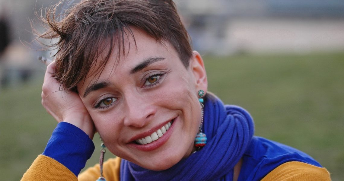 Head shot portrait of a short haired european woman in a yellow sweater wearing a blue scarf.