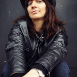 Portrait of a young european woman with red hair, in a black leather jacket and a dark grey hat, sitting with her arms on top of each other, in front of a dark grey background