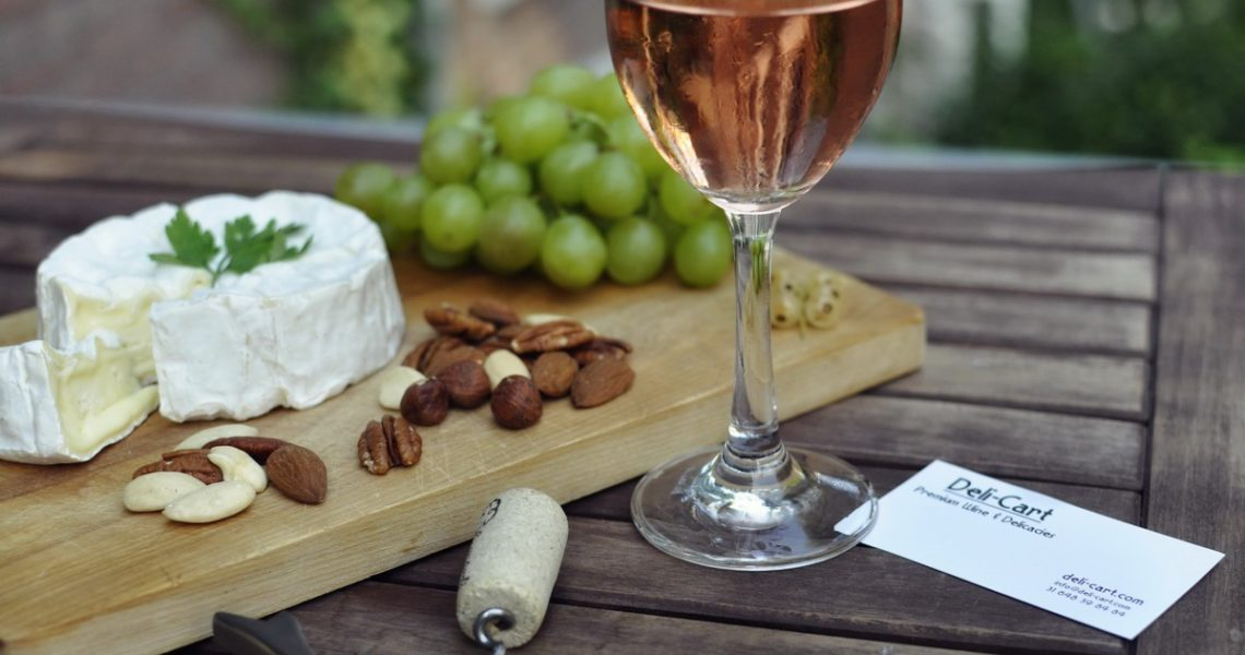 A half-full wine glass with rose wine, a cork screw, a light wood cutting board with brie cheese, almonds and grapes, accompanied by a business card, on top of a natural wood table surface.