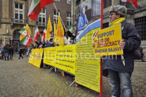 Iran protester holding a sign on the Dam Square - Adam Szuly Photography