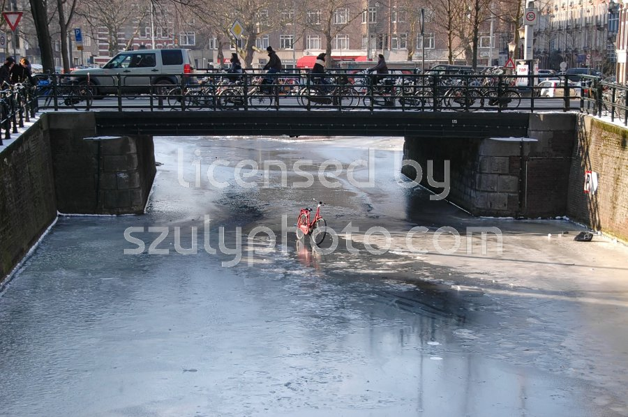Red bicycle on a frozen canal. - Adam Szuly Photography